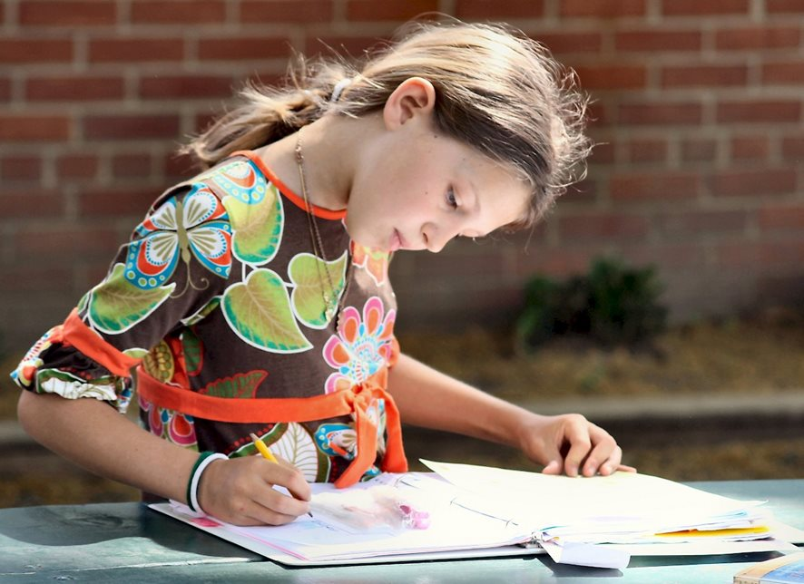 A fifth-grader writes in her main lesson book, where WWS students capture class material over the course of the year, including their thoughts on assigned reading.