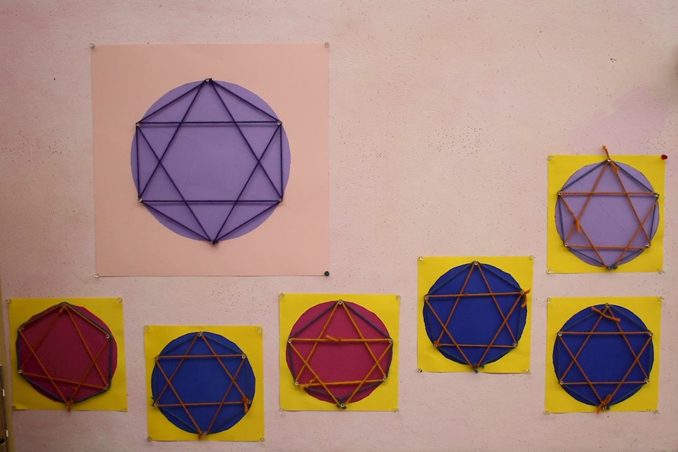 First-graders used string to connect six points on a circle, creating different shapes.