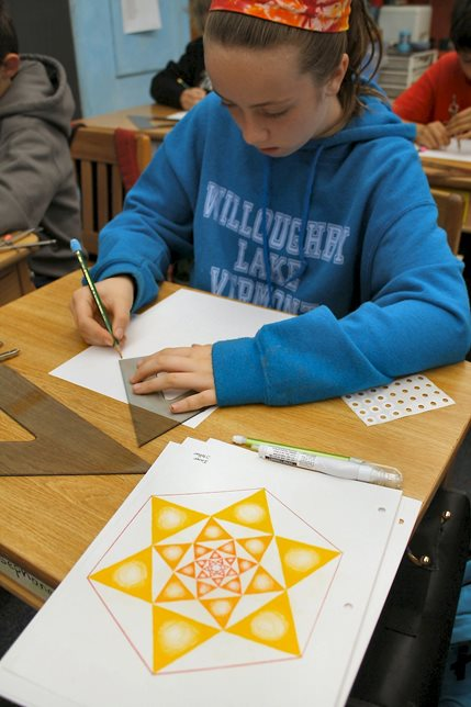A sixth-grader is using a compass and a straight edge to construct a geometric drawing based on divisions of a circle. The drawing of the 6-division of the circle (in the foreground) was constructed using a compass set to the radius of the circle. The compass span is then adjusted to enable the student to bisect the angles of the outer hexagram/hexagon, thus creating the nesting form. This exercise leads to the study of the forms themselves, including the hexagon/hexagram and the equilateral triangle, as well as a study and comparison of various kinds of angles.