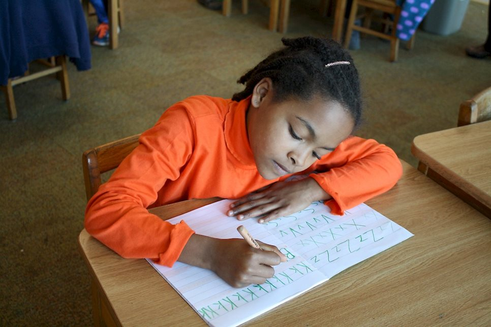 A second-grade student practices writing the alphabet.
